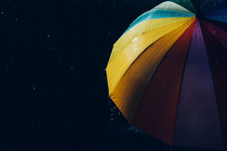 Low angle view of multi colored umbrella against black background