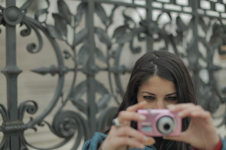 Woman Photographing Through Camera Against Metallic Gate