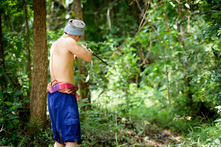 Shirtless Man Aiming With Gun At Forest
