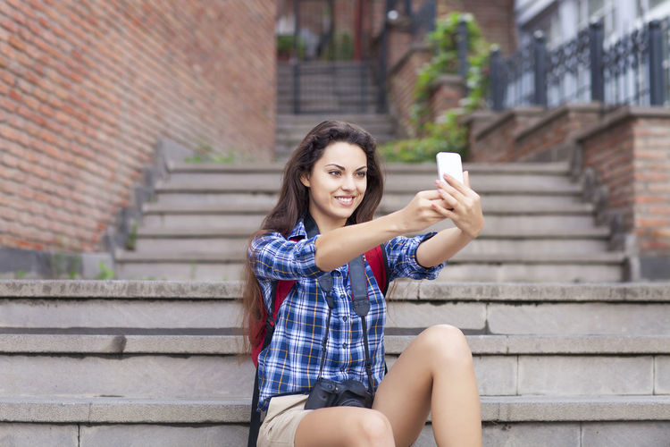 Portrait of young woman using mobile phone while sitting on staircase