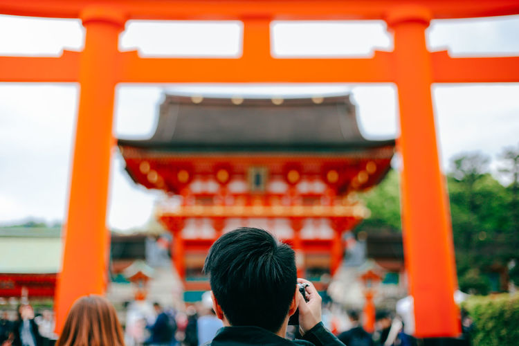Rear View Of Man Photographing At Fushimi Inari-Taisha