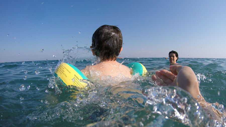 Father And Son Swimming In Sea Against Clear Sky