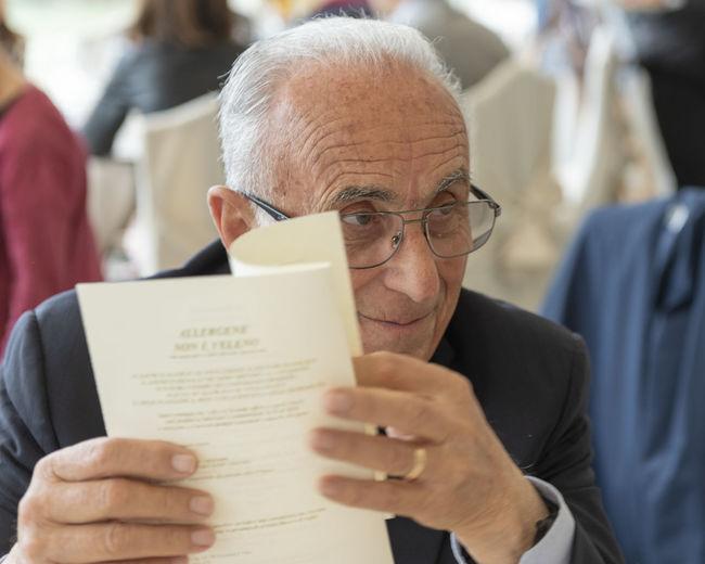 Senior man holding menu while sitting in restaurant