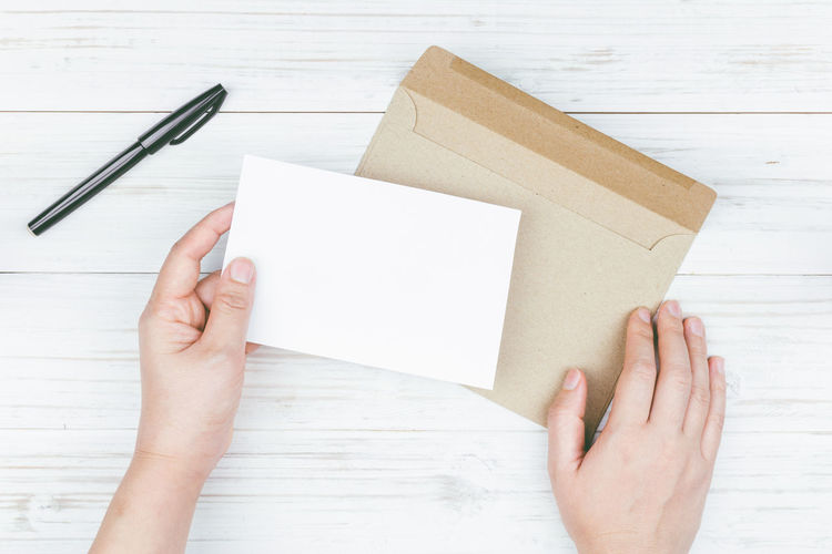 Cropped image of woman holding card with envelop on table