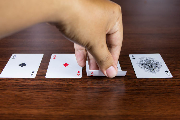 Arts Culture And Entertainment Cards Close-up Finger Gambling Hand High Angle View Holding Human Body Part Human Hand Indoors  Leisure Activity Leisure Games Luck One Person Relaxation Selective Focus Table Women Wood - Material