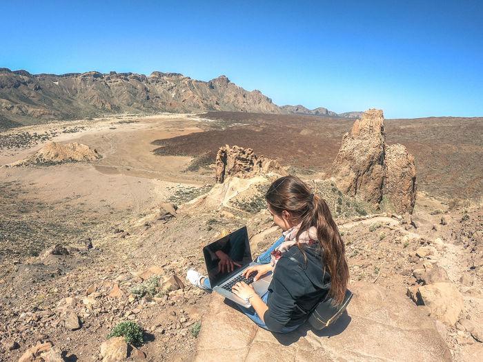 Teenage girl using laptop while sitting on rock at desert