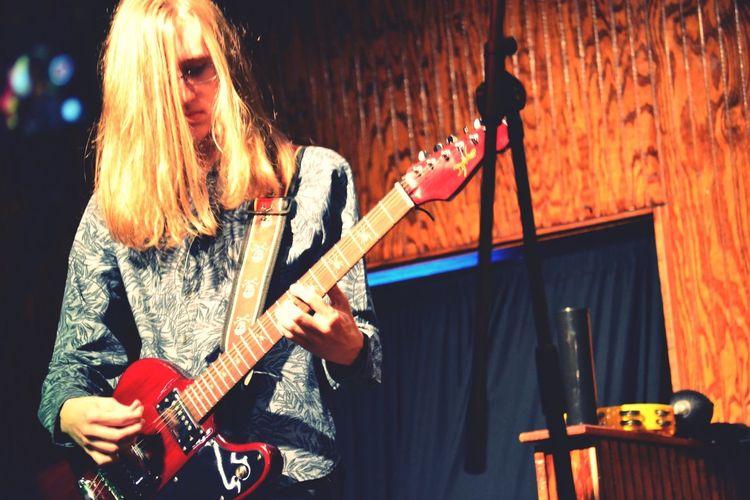 Man with long hair playing guitar at concert