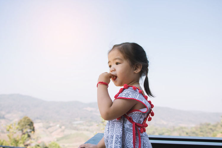 Side view of cute girl eating fruit looking away against clear sky