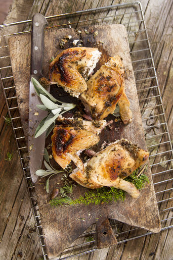 High Angle View Of Roast Chicken On Cutting Board With Rack Over Wooden Table