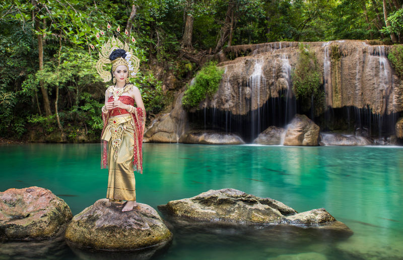 Portrait of beautiful young woman wearing crown and traditional clothing while standing on rock against lake at forest
