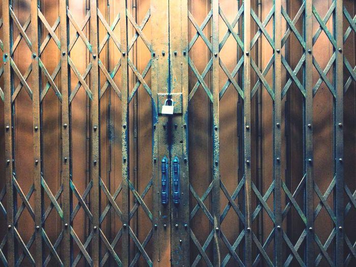 Full frame shot of metallic gate with padlock