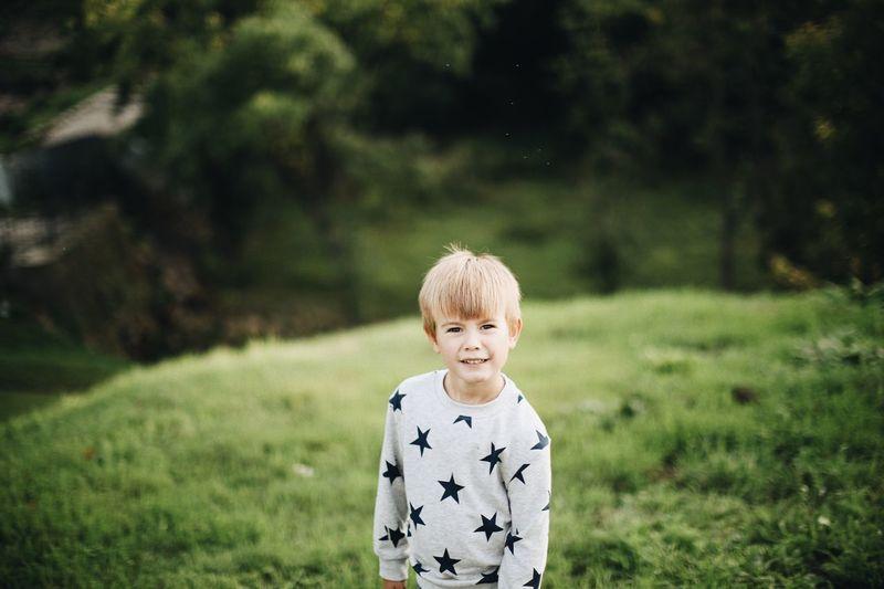 Portrait of cute boy standing on field