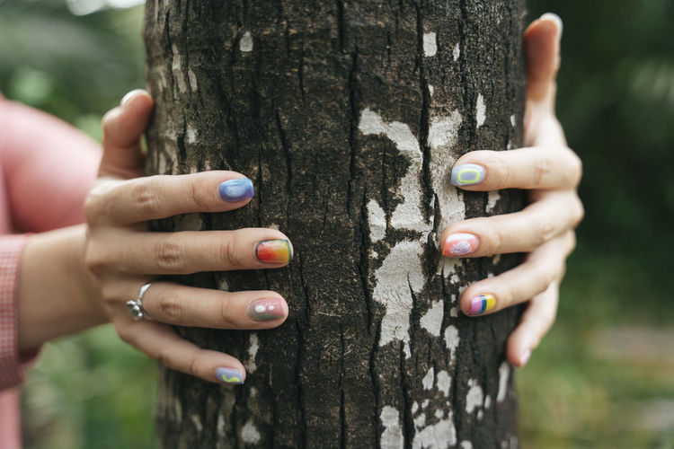 Close-up of hand holding tree trunk