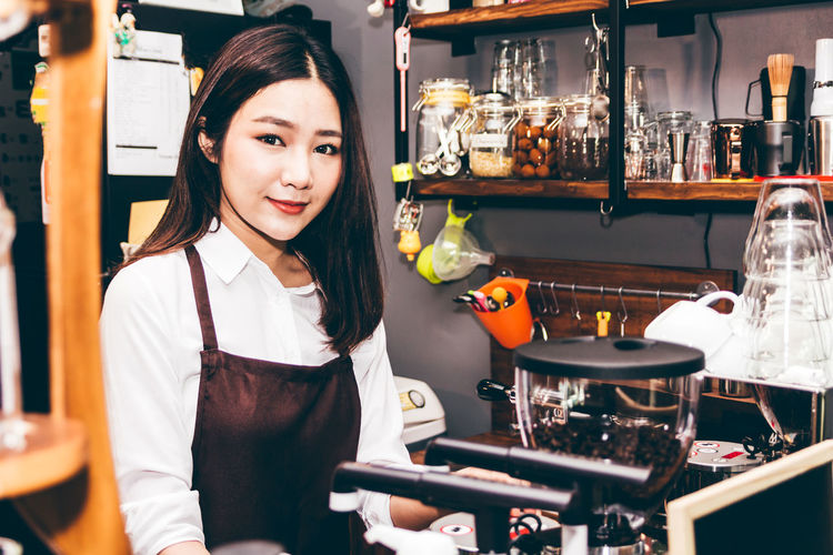 Women Barista using coffee machine for making coffee in the cafe Adult Beautiful Woman Emotion Food And Drink Front View Glass Hairstyle Holding Indoors  Lifestyles Looking At Camera Occupation One Person Portrait Real People Smiling Standing Waist Up Women Young Adult Young Women