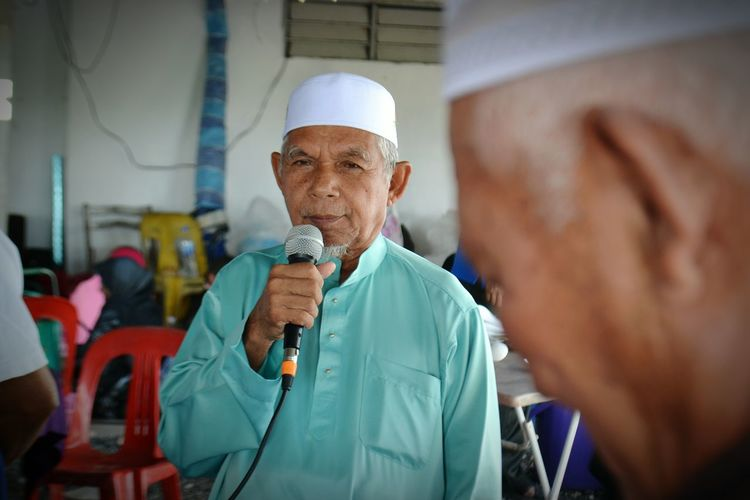 Senior Man Using Microphone While Standing Indoors