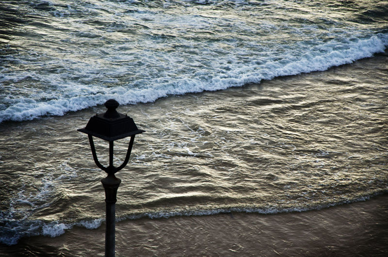 High angle view of lamp post by sea