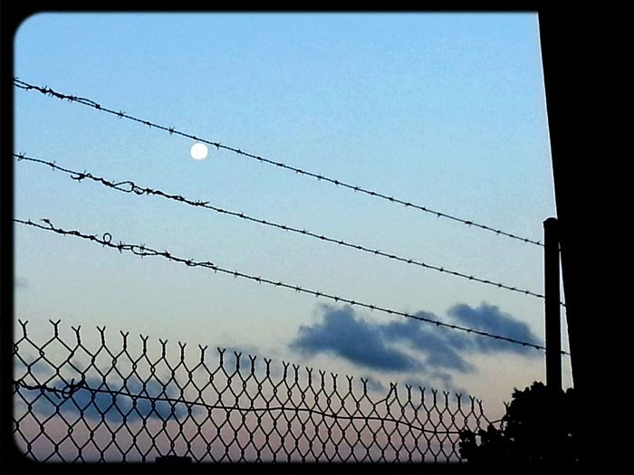Full Moon thru Barbed Wire fence in Footscray