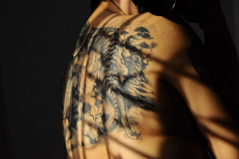 Midsection of man back with tattoo in darkroom