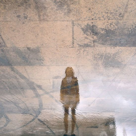 Reflection of person on water at footpath in rainy season