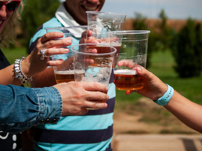Cropped hands of people drinking beer in glass
