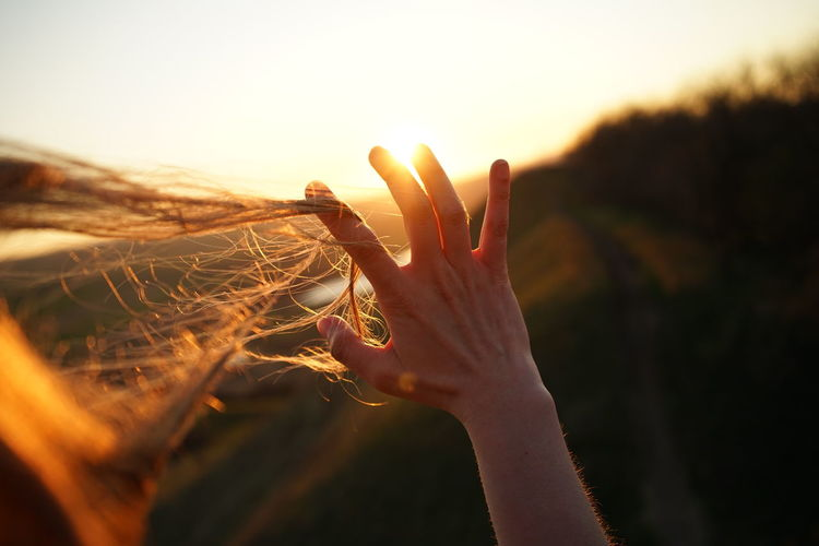 Cropped hand with tousled hair during sunset