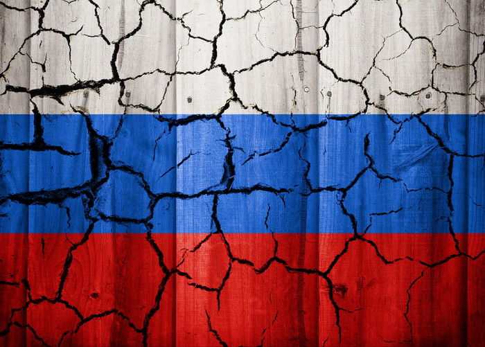 Full frame shot of cracked wall with russian flag