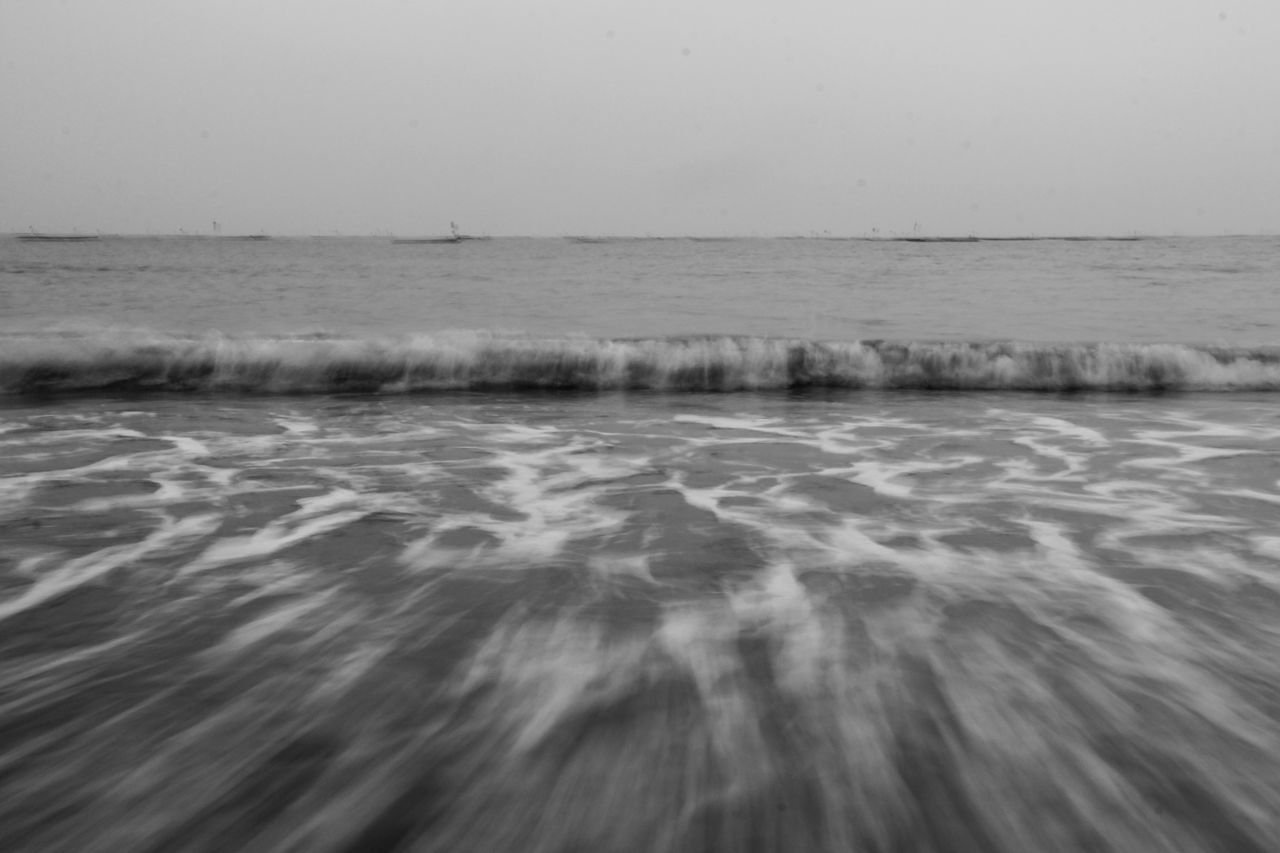 High Angle View Of Waves Rushing Towards Shore Against Sky