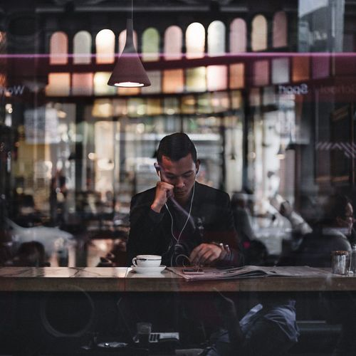 Man Using Phone On Table In Cafe Seen Through Window