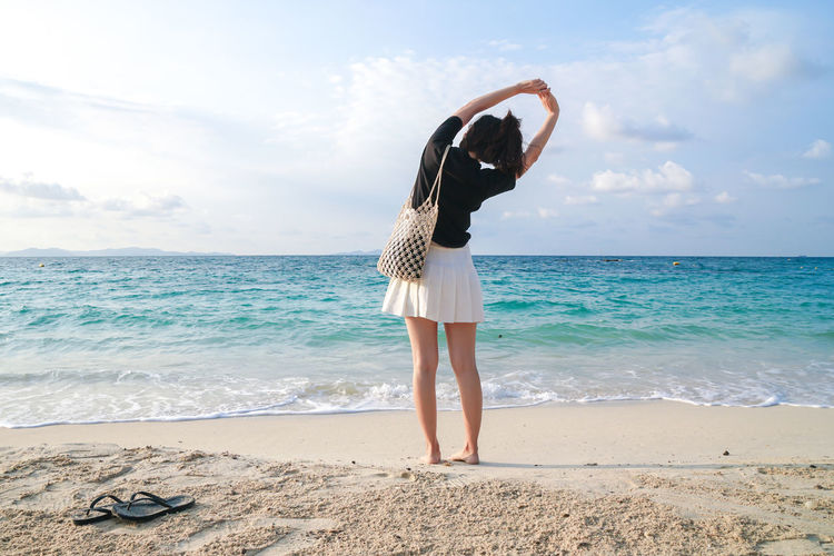 Rear view of person standing at beach against sky