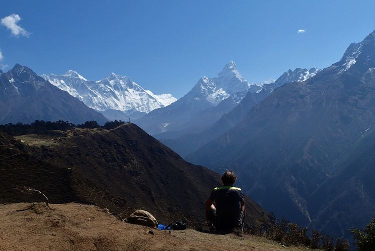 Rear view of man sitting against snowcapped mountains