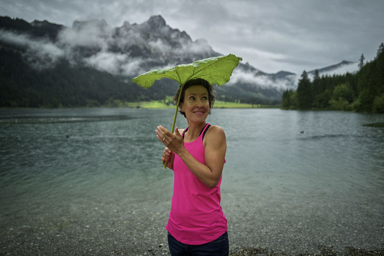 Portrait of woman standing by lake against mountains