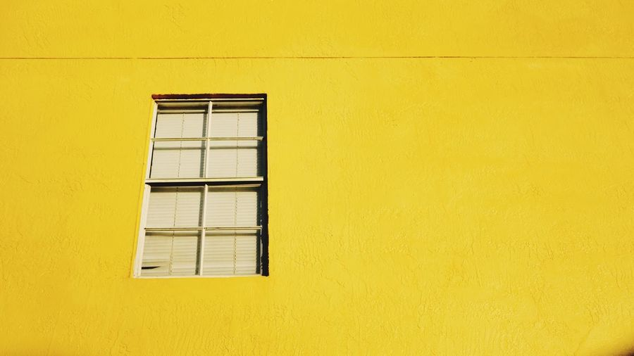 Low angle view of window on yellow wall