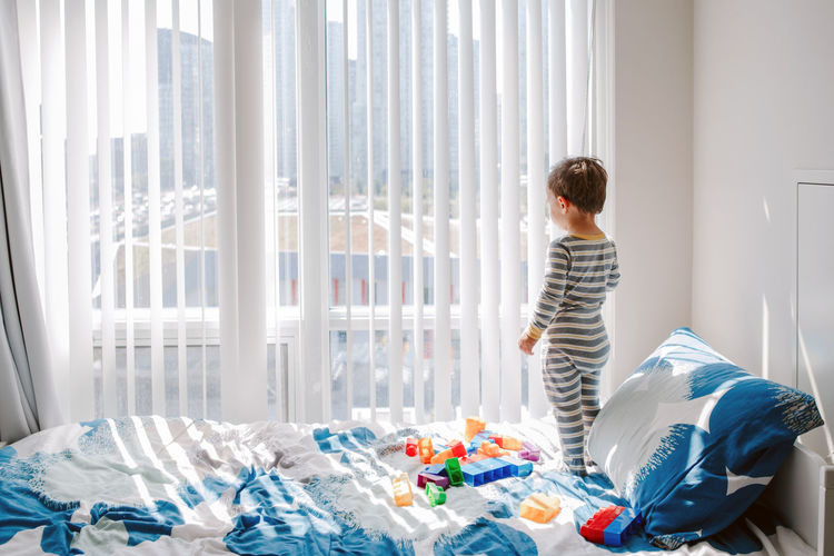 Cute little boy toddler standing on bed in room and looking into window waiting expecting someone.