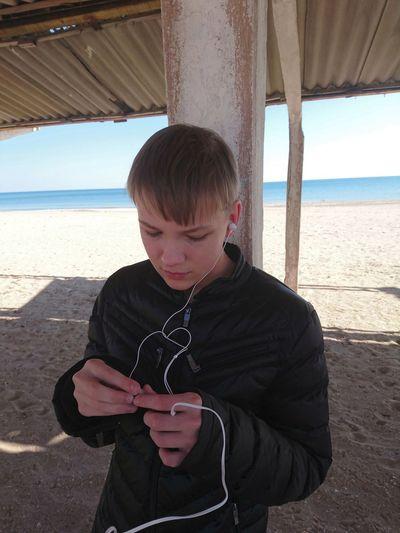 Full length of boy using mobile phone at sea