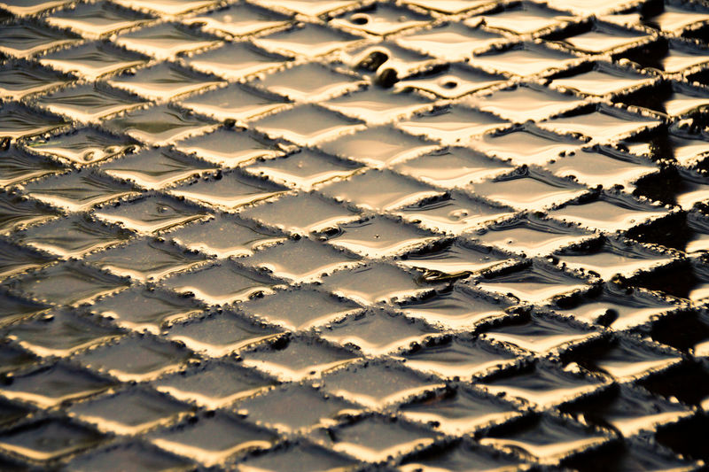 Full frame shot of wet metal grate