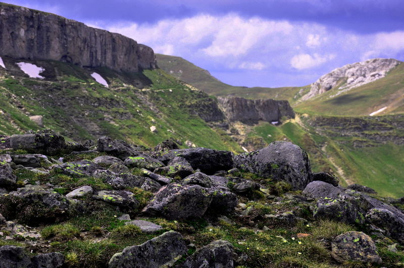 Rocks on grassy mountain against cloudy sky