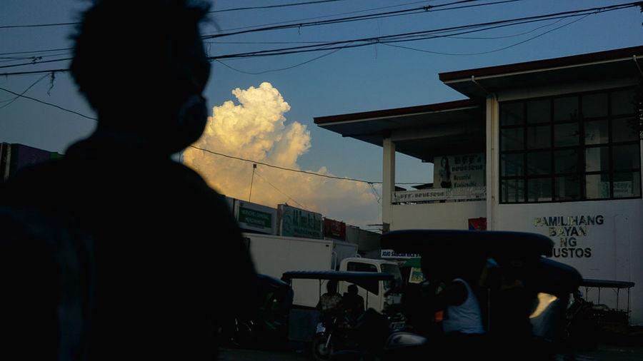 Silhouette people standing on street against sky