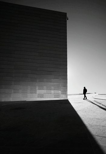 Silhouette man walking by building