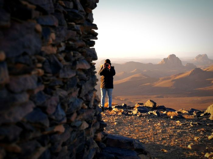 Full Length Of Man Photographing With Smart Phone While Standing At Desert