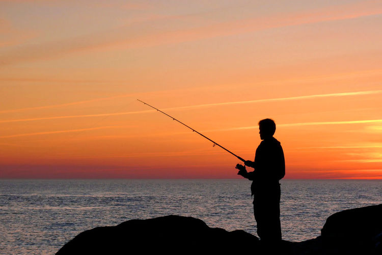 Silhouette Of Person Fishing At Sunset