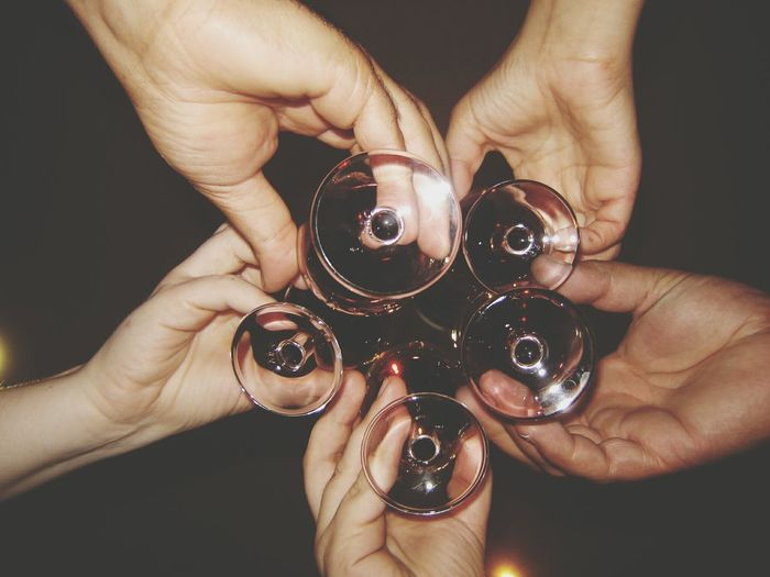 Cropped Hands Of Friends Toasting Wineglasses At Night