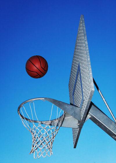 Low Angle View Of Basketball Over Hoop Against Blue Sky