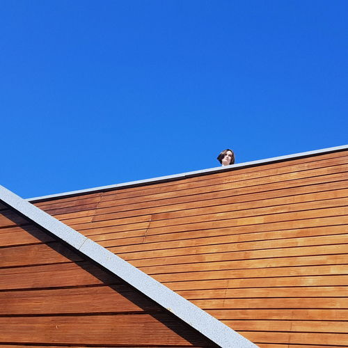 Low Angle View Of Woman Standing By Wooden Wall Against Clear Blue Sky