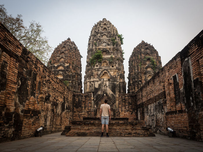 Rear view of man standing in front of buddhist temple, sukhothai, thailand