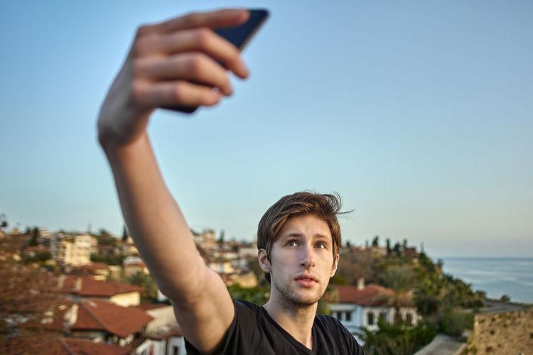 Portrait of man using smart phone against sky