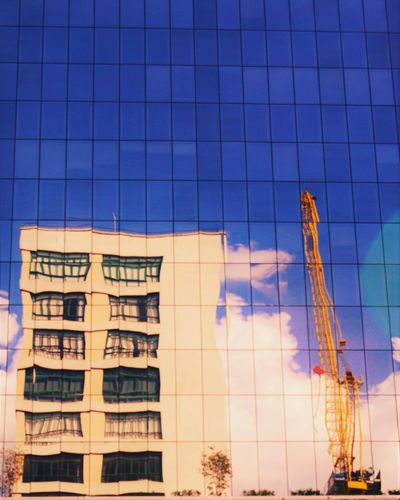 Low angle view of building and crane reflecting on glass windows