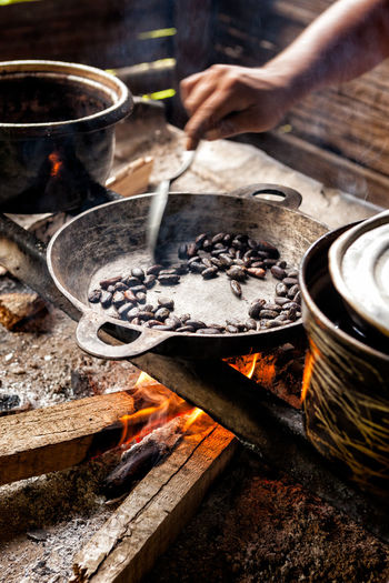 Close up of hand roasting cocoa bean on frying pan