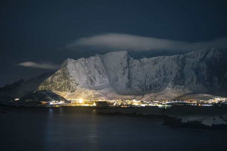 Illuminated snowcapped mountains against sky at night during winter