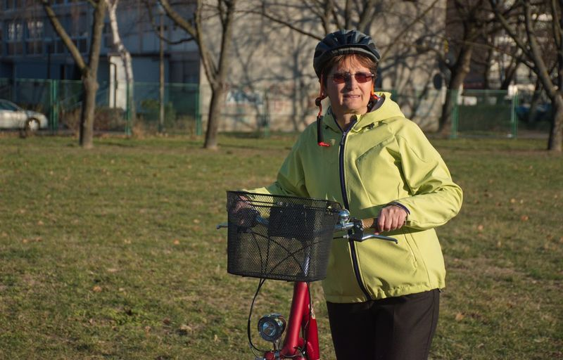 One Person Field Clothing Real People Tree Three Quarter Length Front View Portrait Adult Day Plant Lifestyles Standing Leisure Activity Warm Clothing Outdoors Bike Bicycle Woman Mature Adult Helmet Basket Yellow Grass Glasses