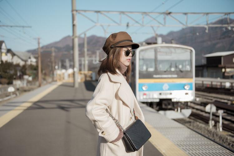 Woman wearing hat standing on railroad station platform